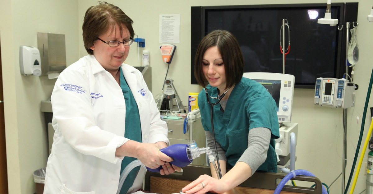 Graduate nursing student works in Hershey Medical Center under supervision.