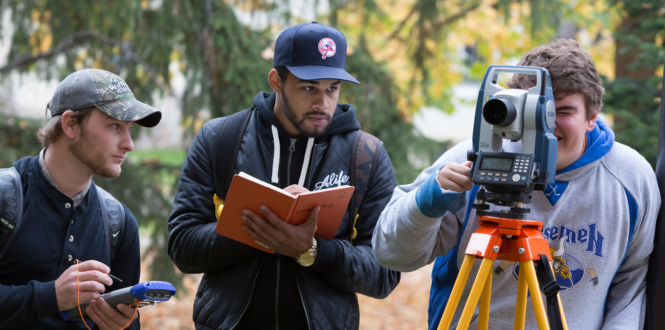 Three students using surveying equipment and taking notes