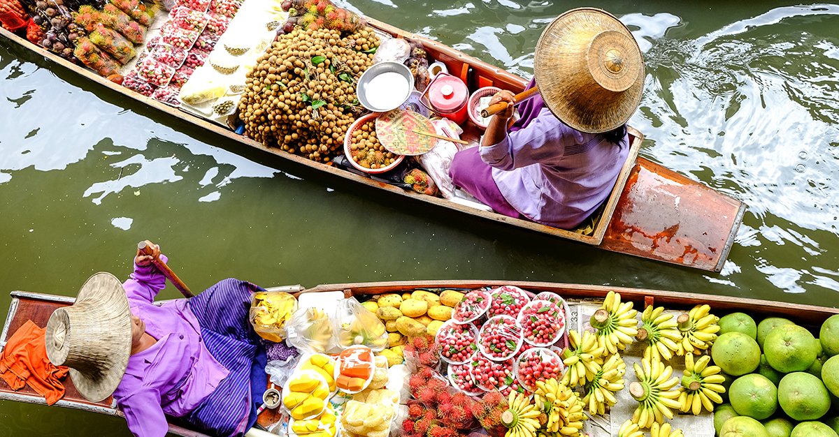 Two women row canoes filled with produce at the Ratchaburi floating market in Thailand.