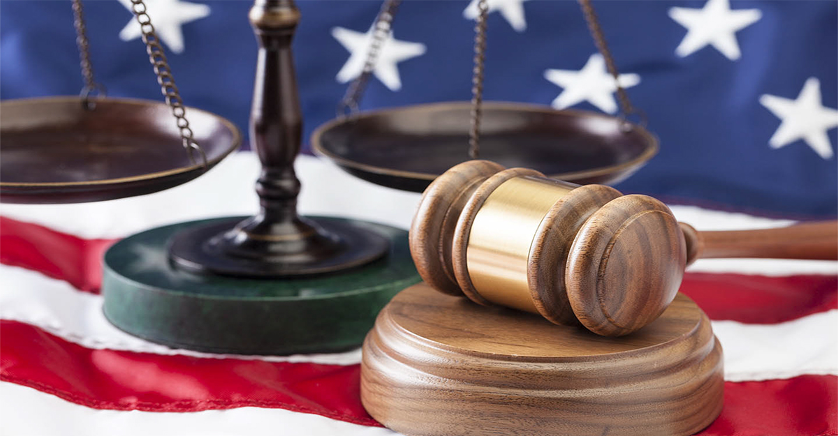 Scales of justice and gavel sitting on United States flag
