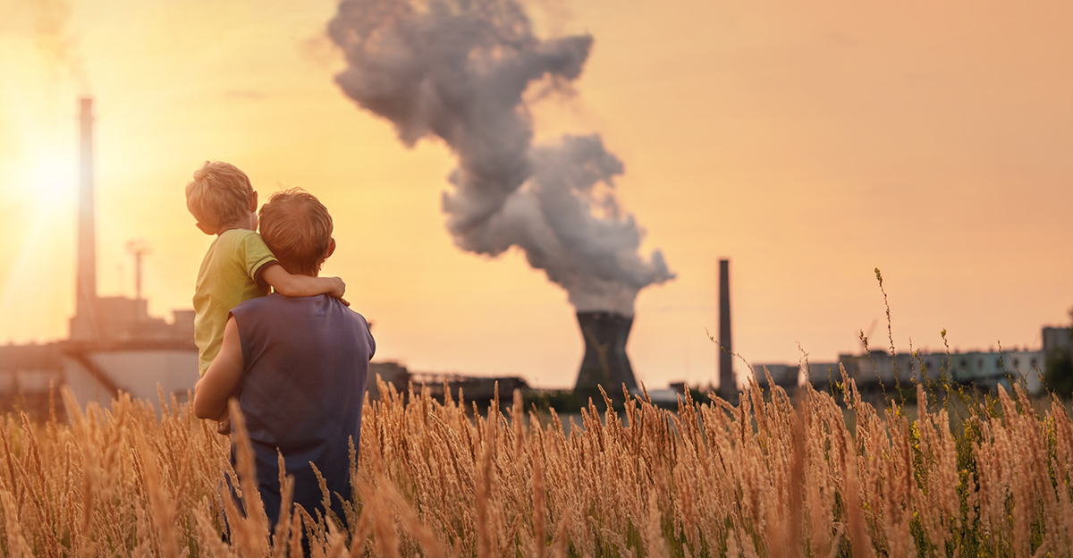 Father and son view industrial pollution while standing in a wheat field.