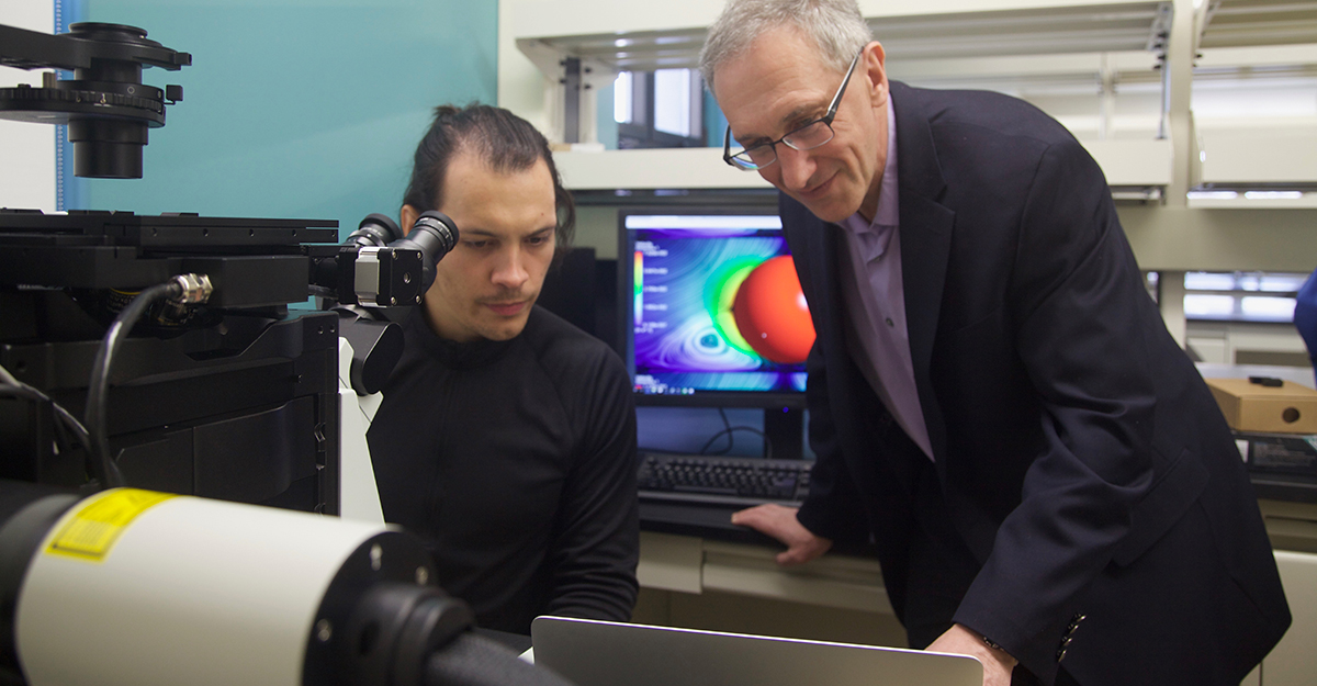 two engineers looking at results from a high-powered microscope