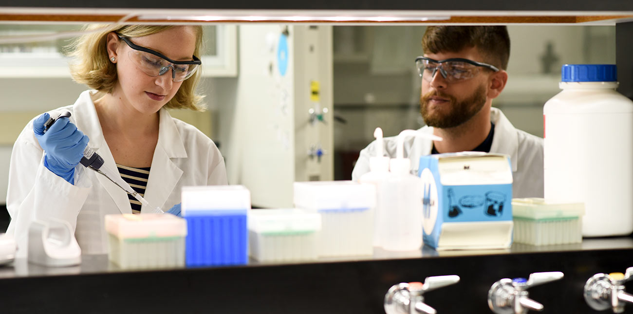 Female and male working at a lab bench using a pipette