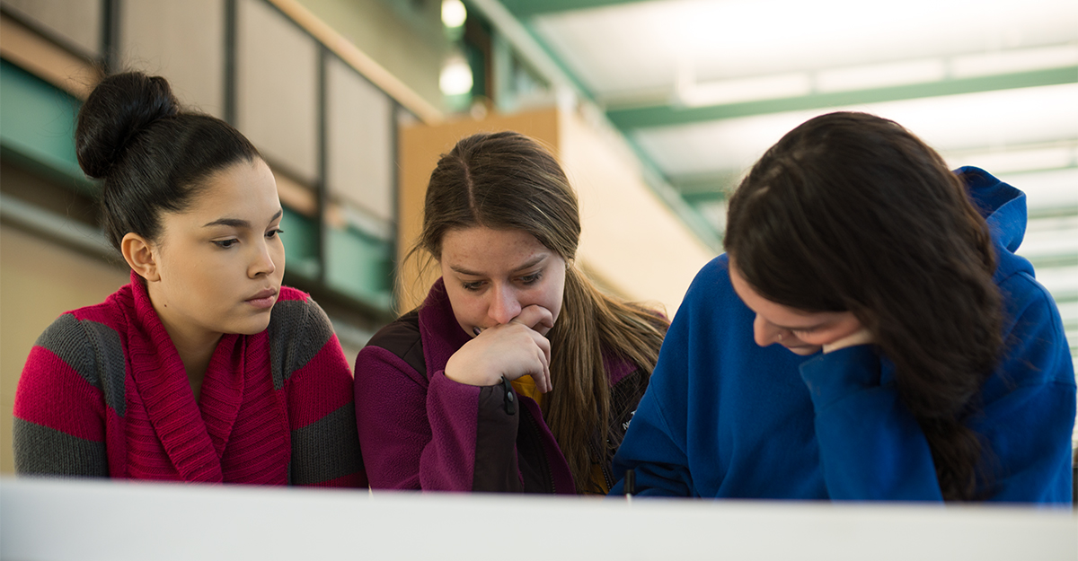 Three students working on a project in the classroom