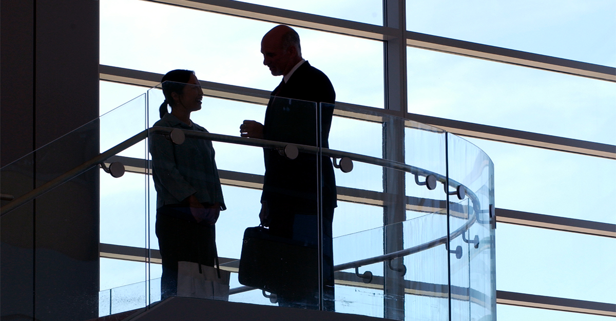 Silhouettes of two business professionals contrasting against a building