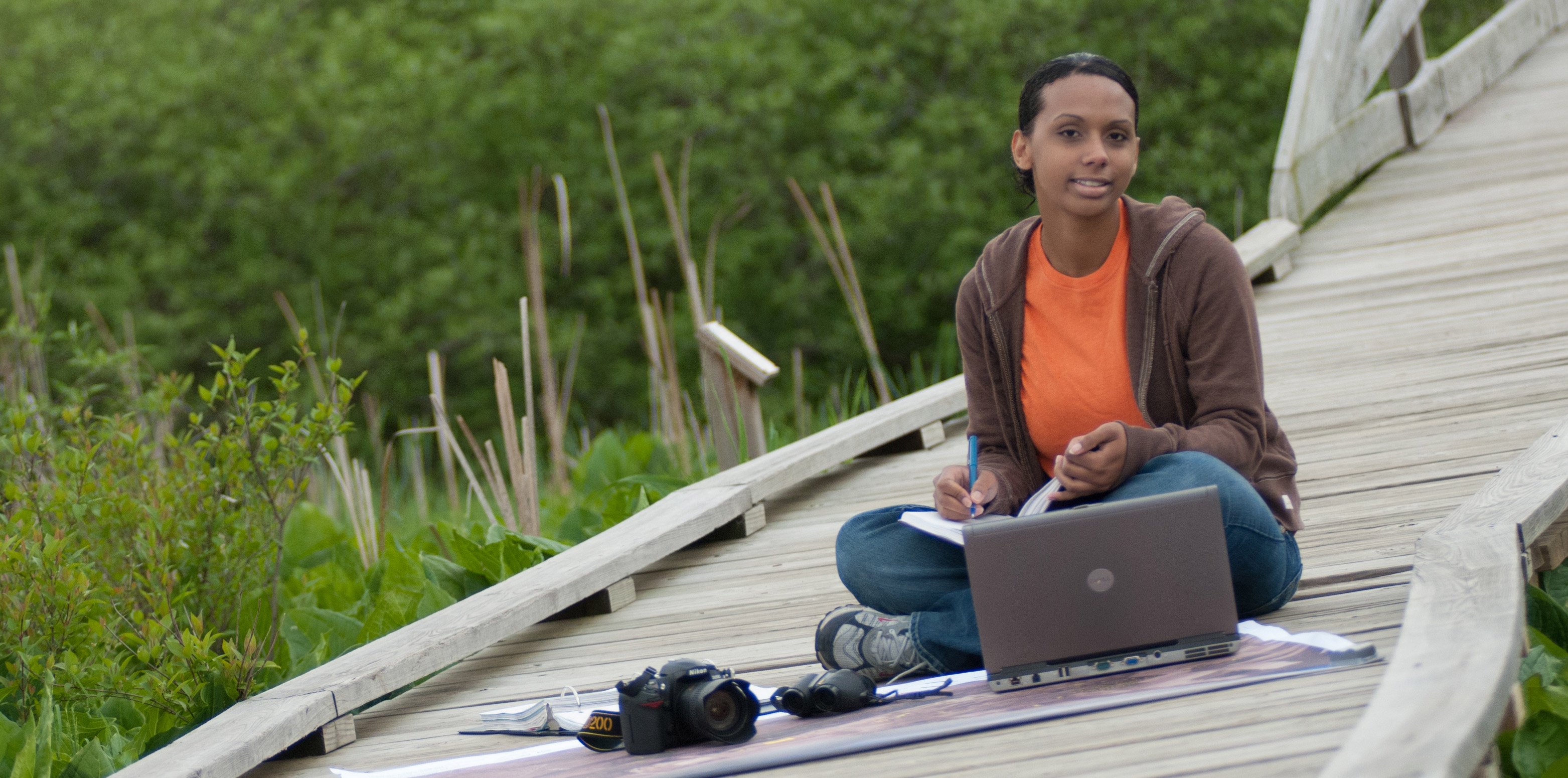 Student in wetlands with map and laptop