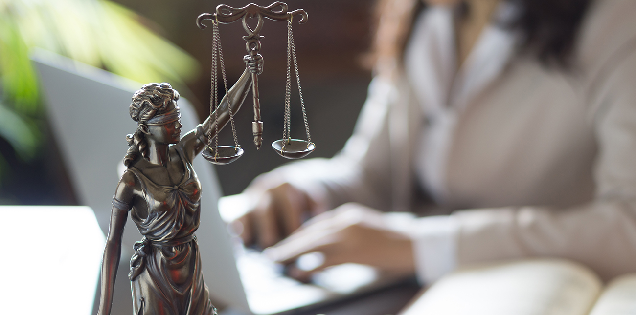 Individual working in the background with scales of justice in foreground