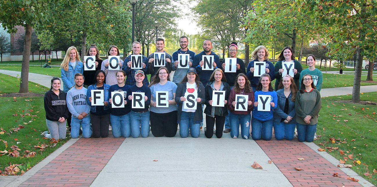 A group of Penn State College of Ag Sciences students spell out C-O-M-M-U-N-I-T-Y  F-O-R-E-S-T-R-Y by holding placards with the individual letters