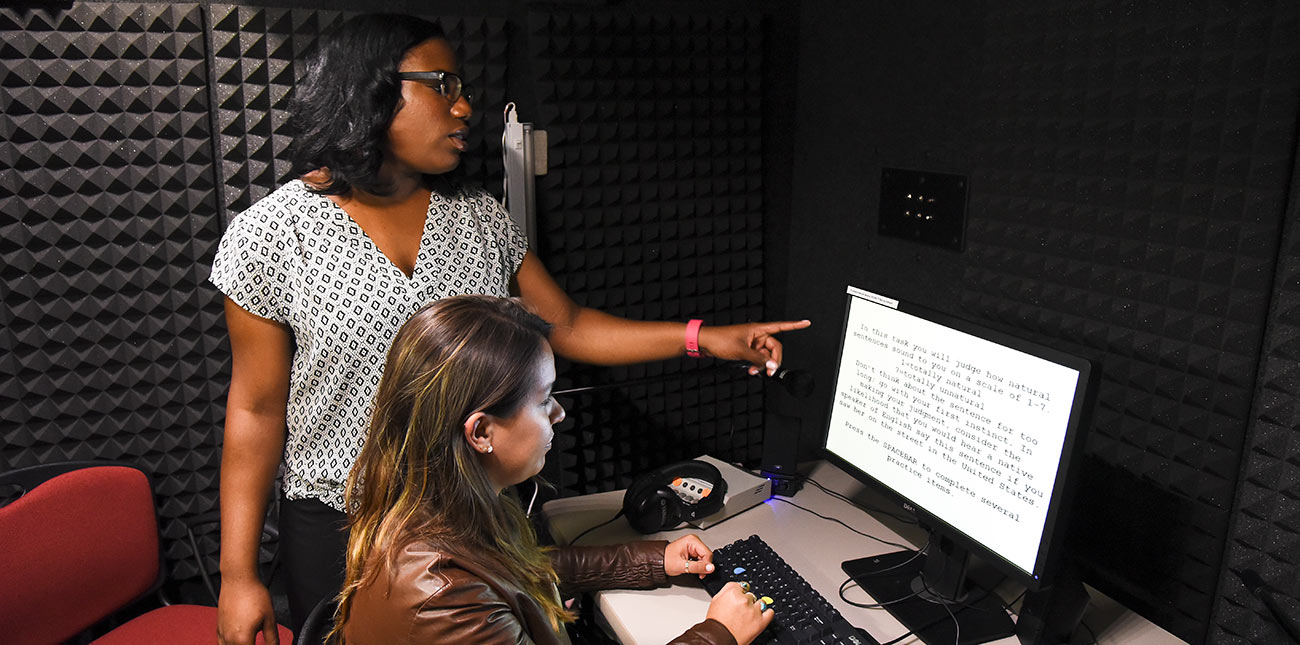 Two female students in an acoustic sound booth reading text on a computer screen