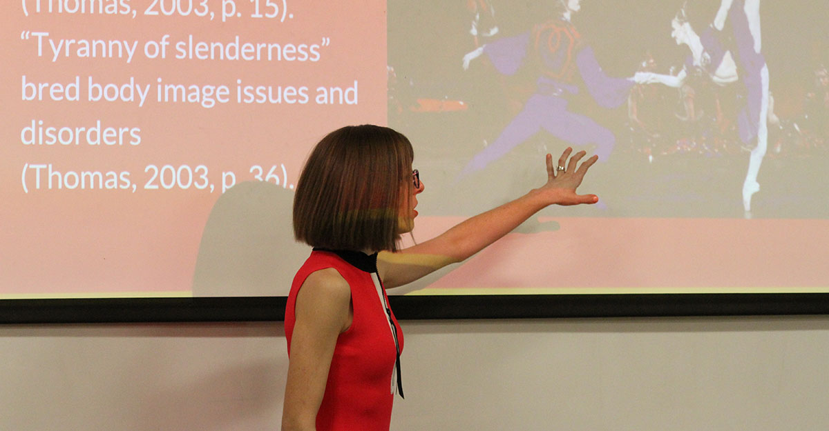 Grad student gesturing at her onscreen presentation