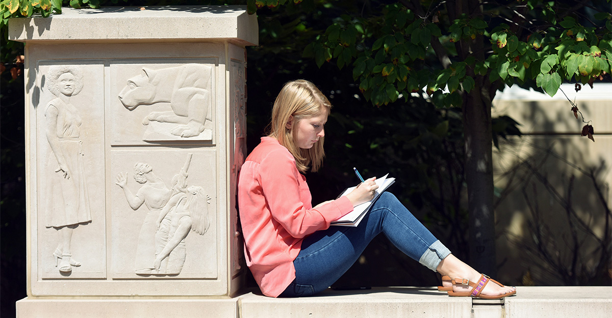 Student leaning against column while working on a writing assignment
