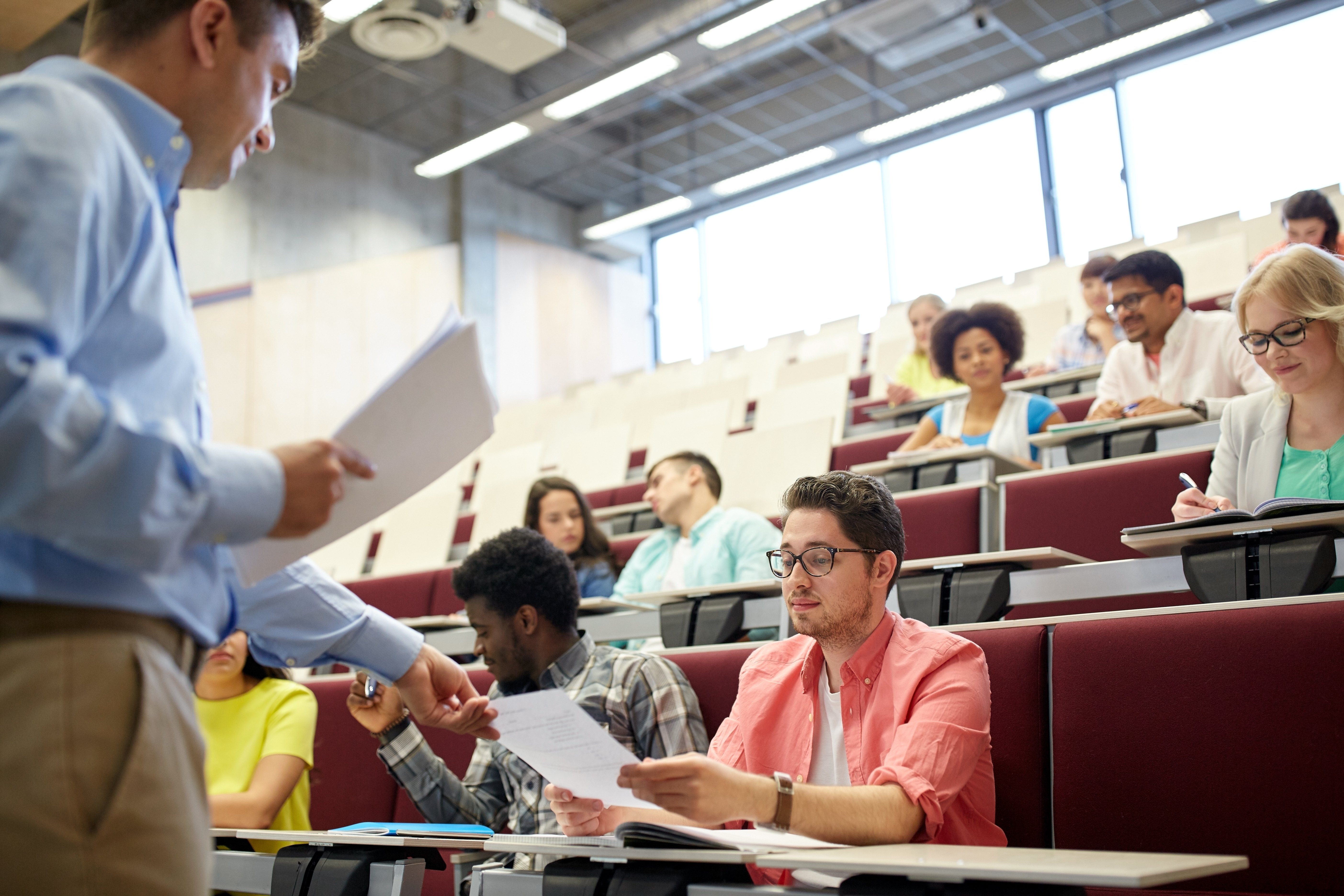Classroom of professionally dressed students receiving papers from professor