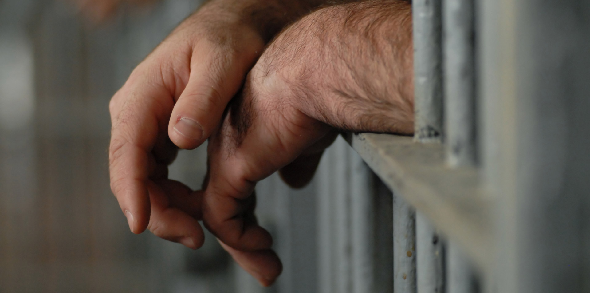 Two hands poking between the bars of a jail cell