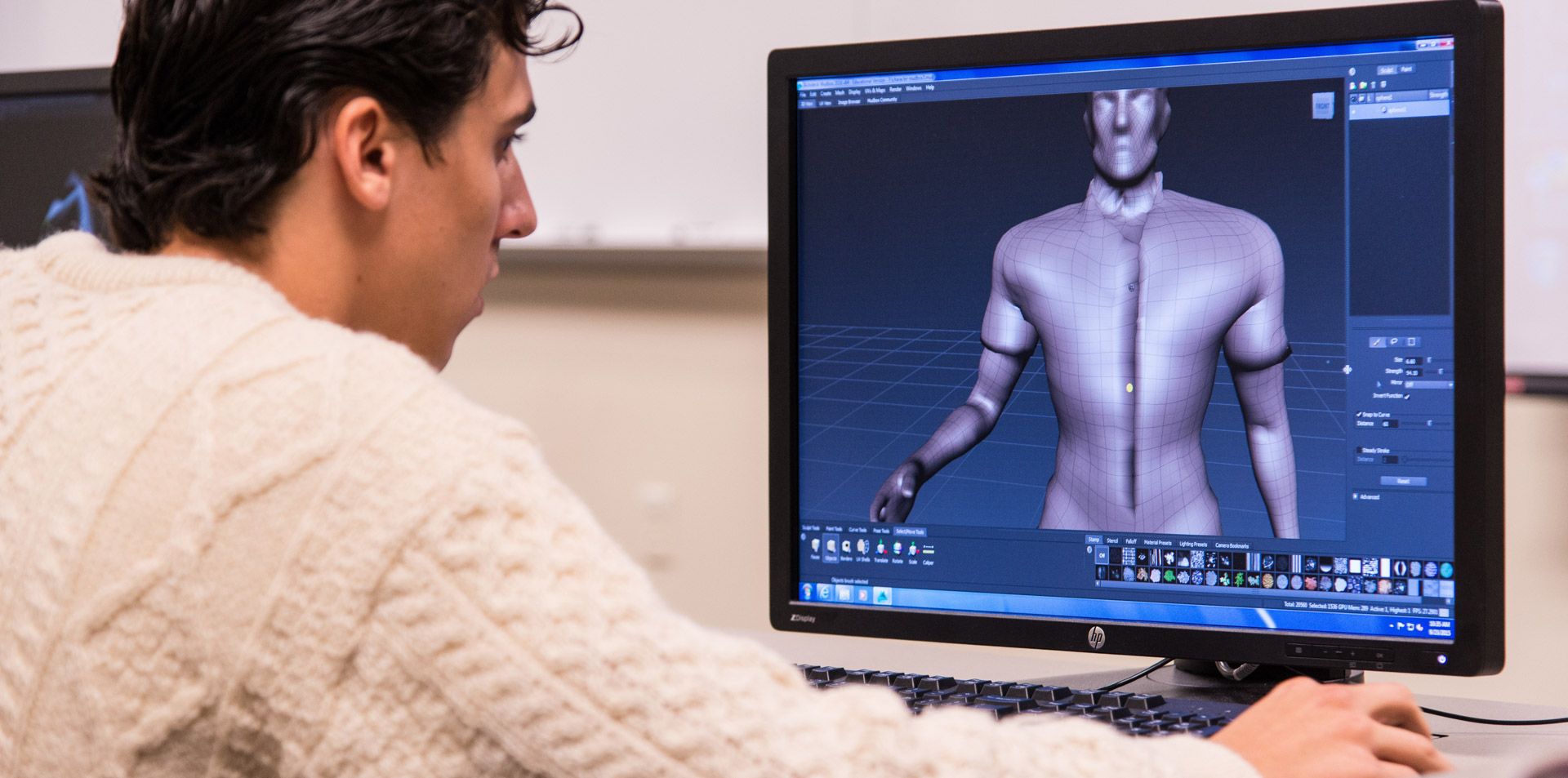 Student looking at a digital rendering of a male torso on computer screen