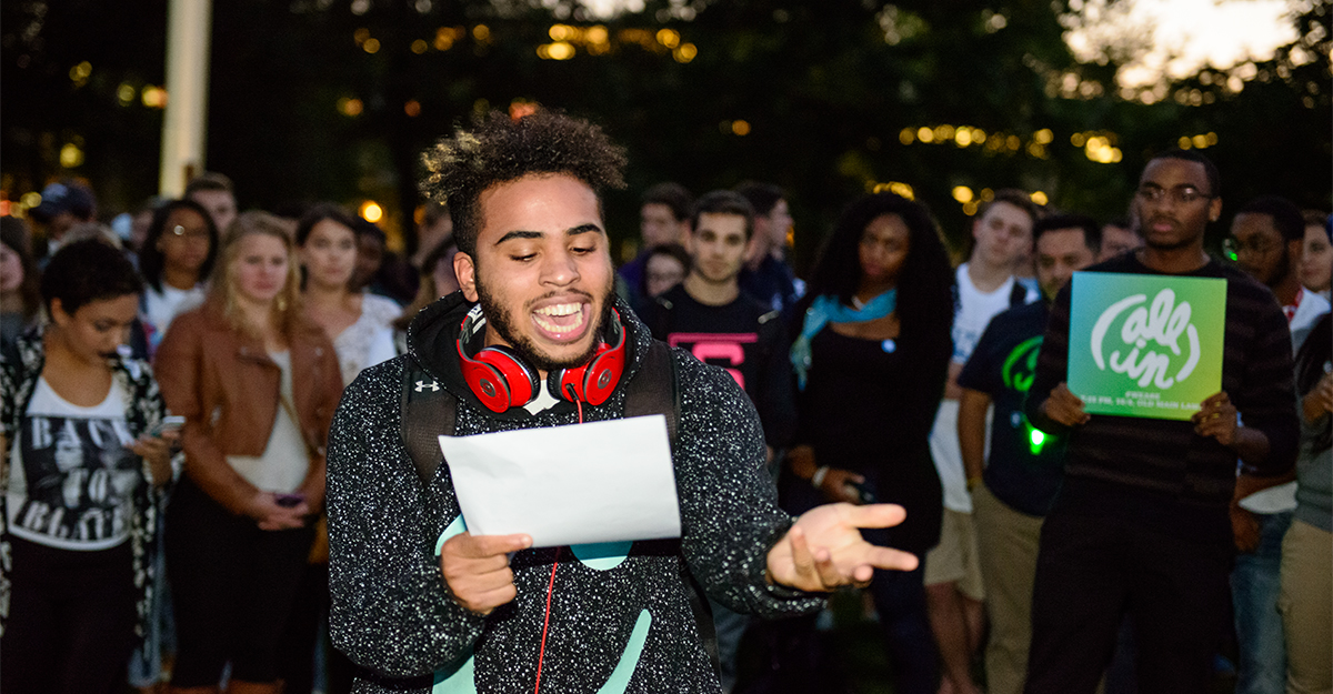 Photo of student giving a speech at an All In event in front of Old Main