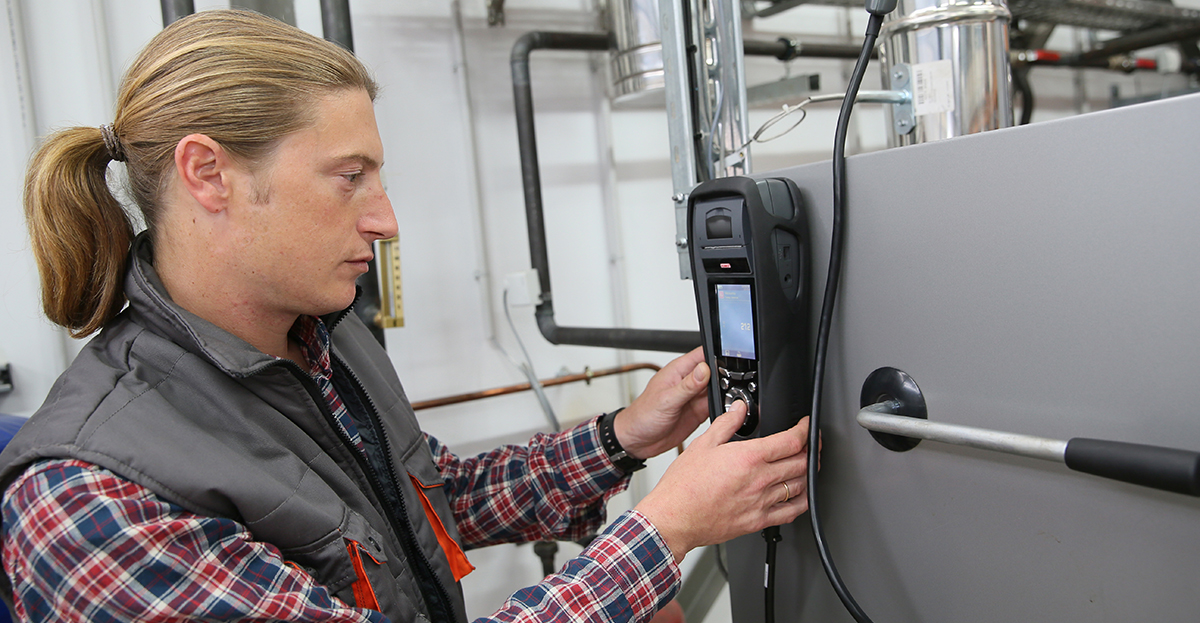 Technician checks temperature on a heat pump using electronic device.