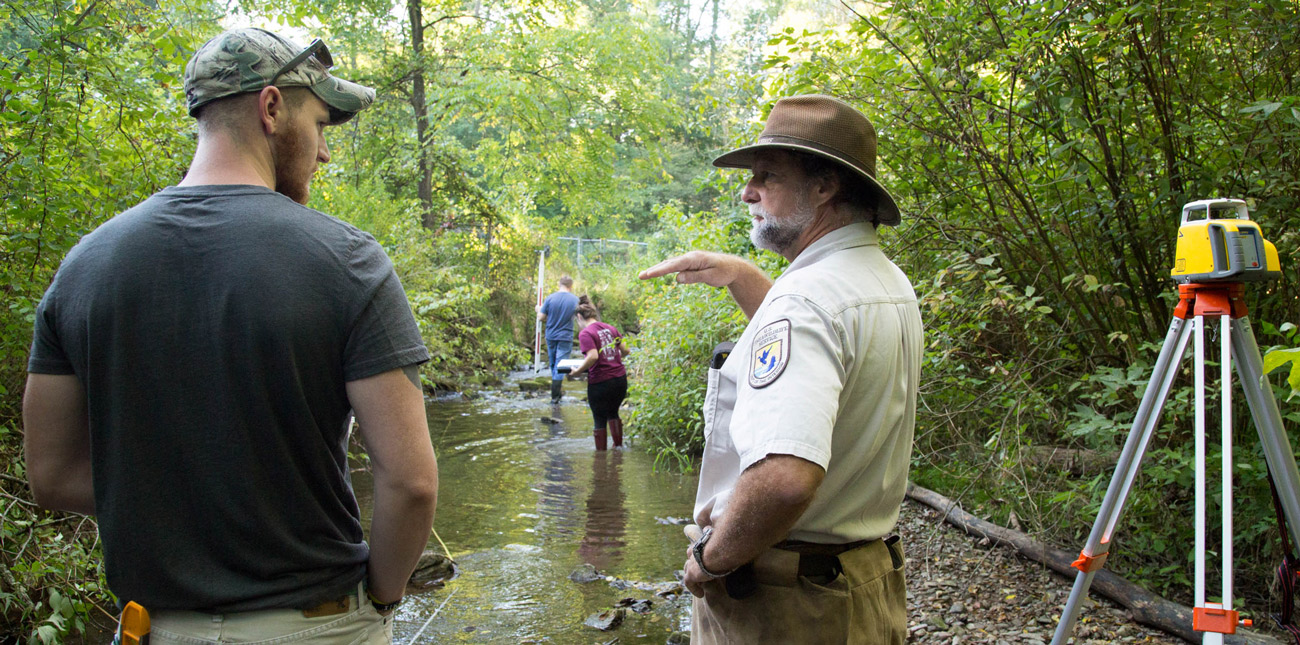 Student and natural resource officer surveying stream
