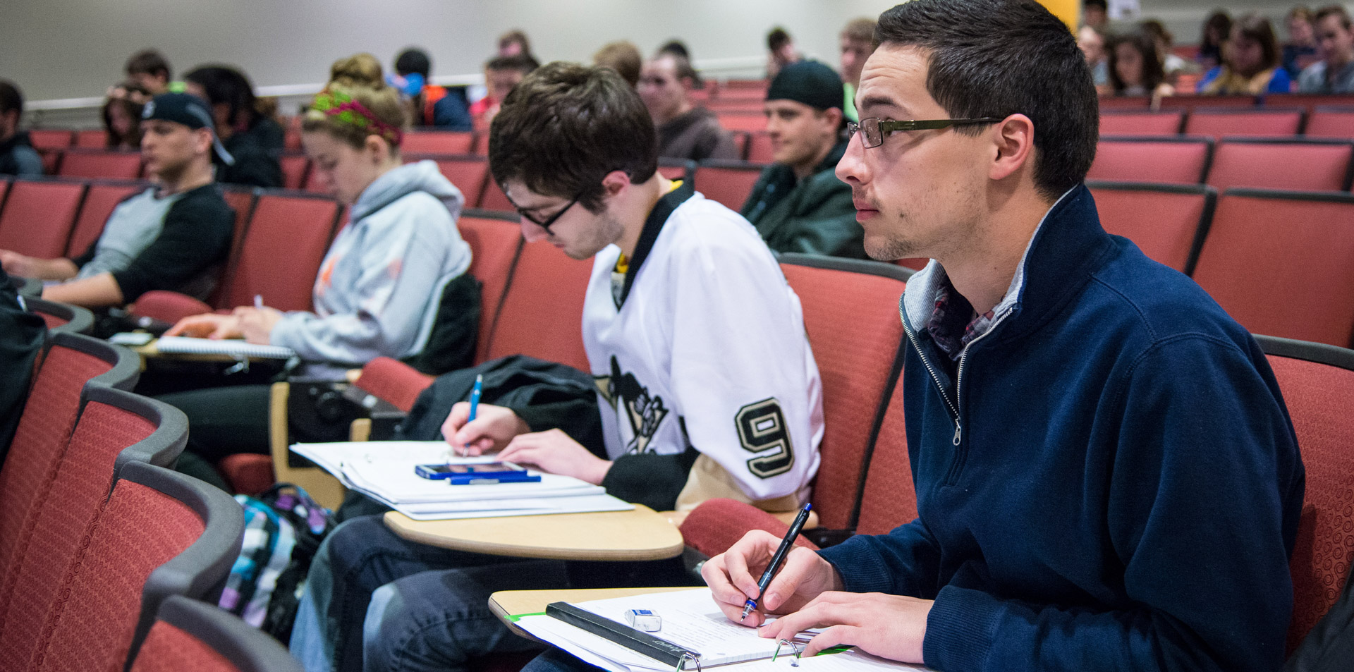 Students using armchair desks to take notes during a class in Reed Auditorium
