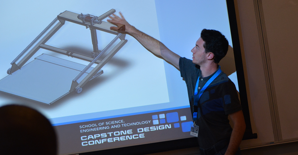 Student gesturing at onscreen rendering of an engineered lift device