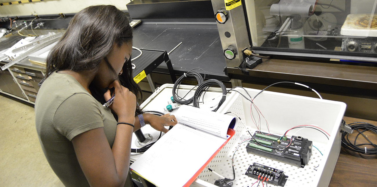 Student taking notes while studying electrical equipment