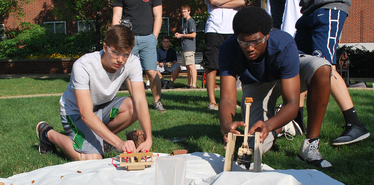 Two students testing catapult designs