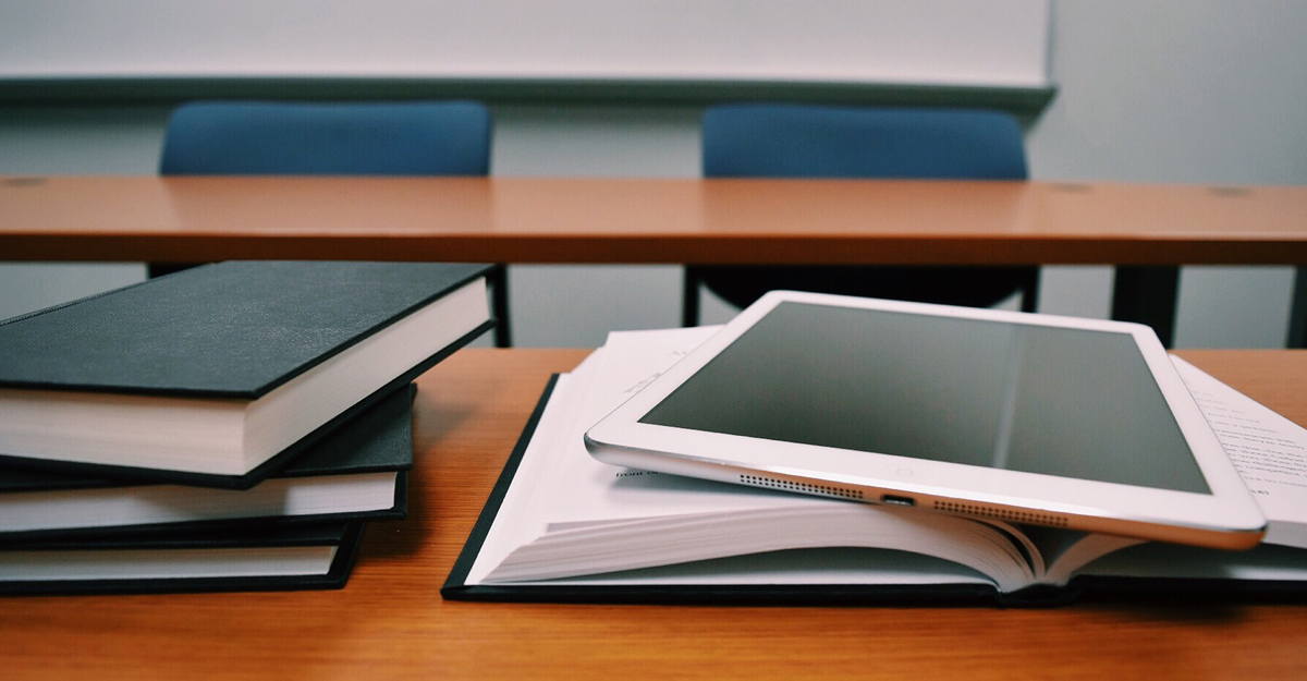 Books and tablet set on a classroom desk.