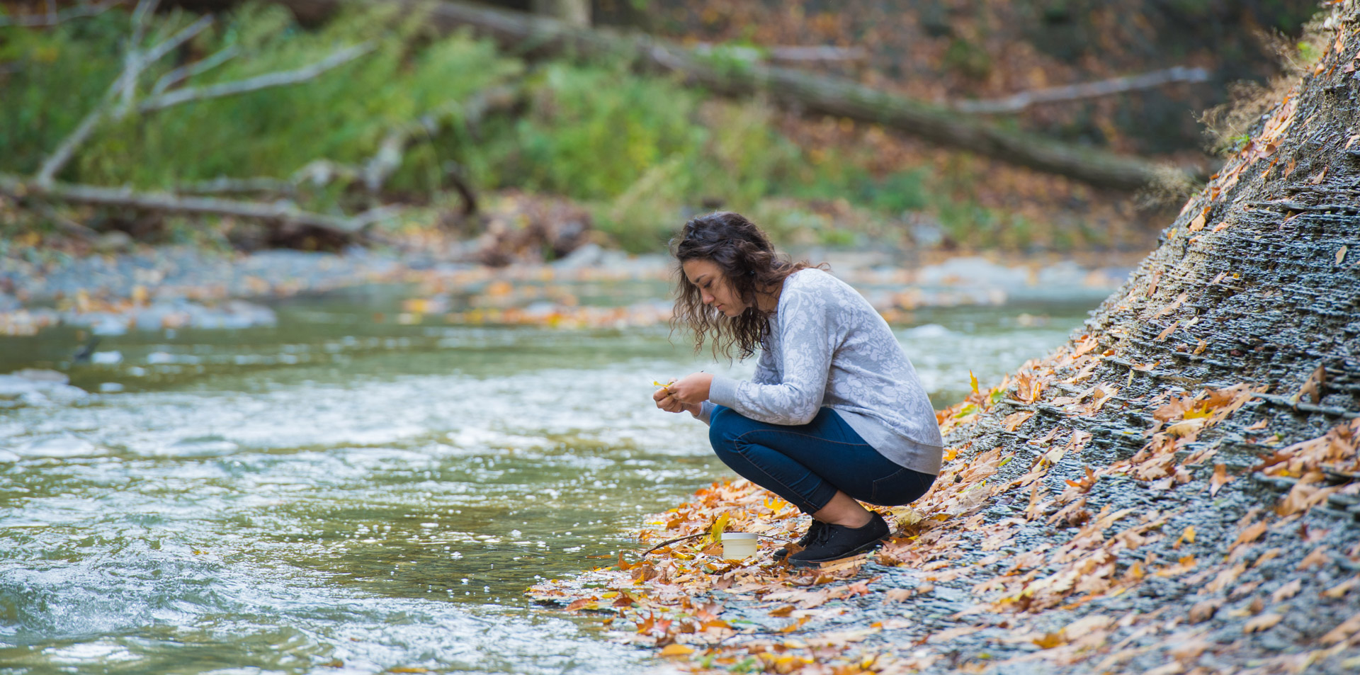 Student crouching beside a creek to collect water samples