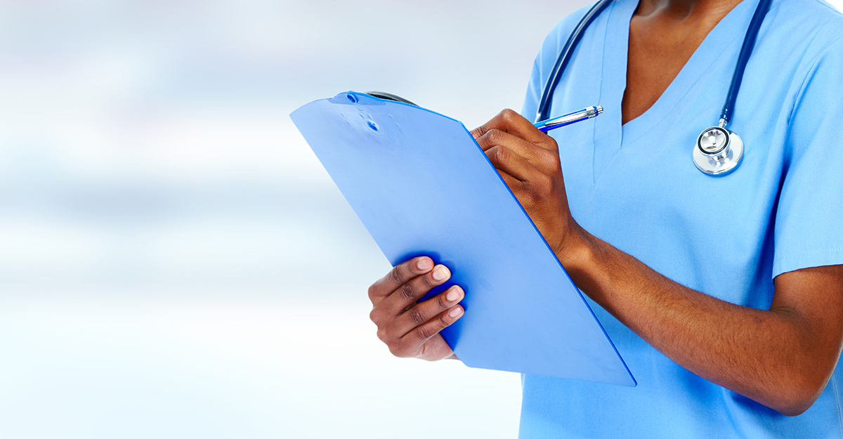Close up of nurse taking notes on clipboard.