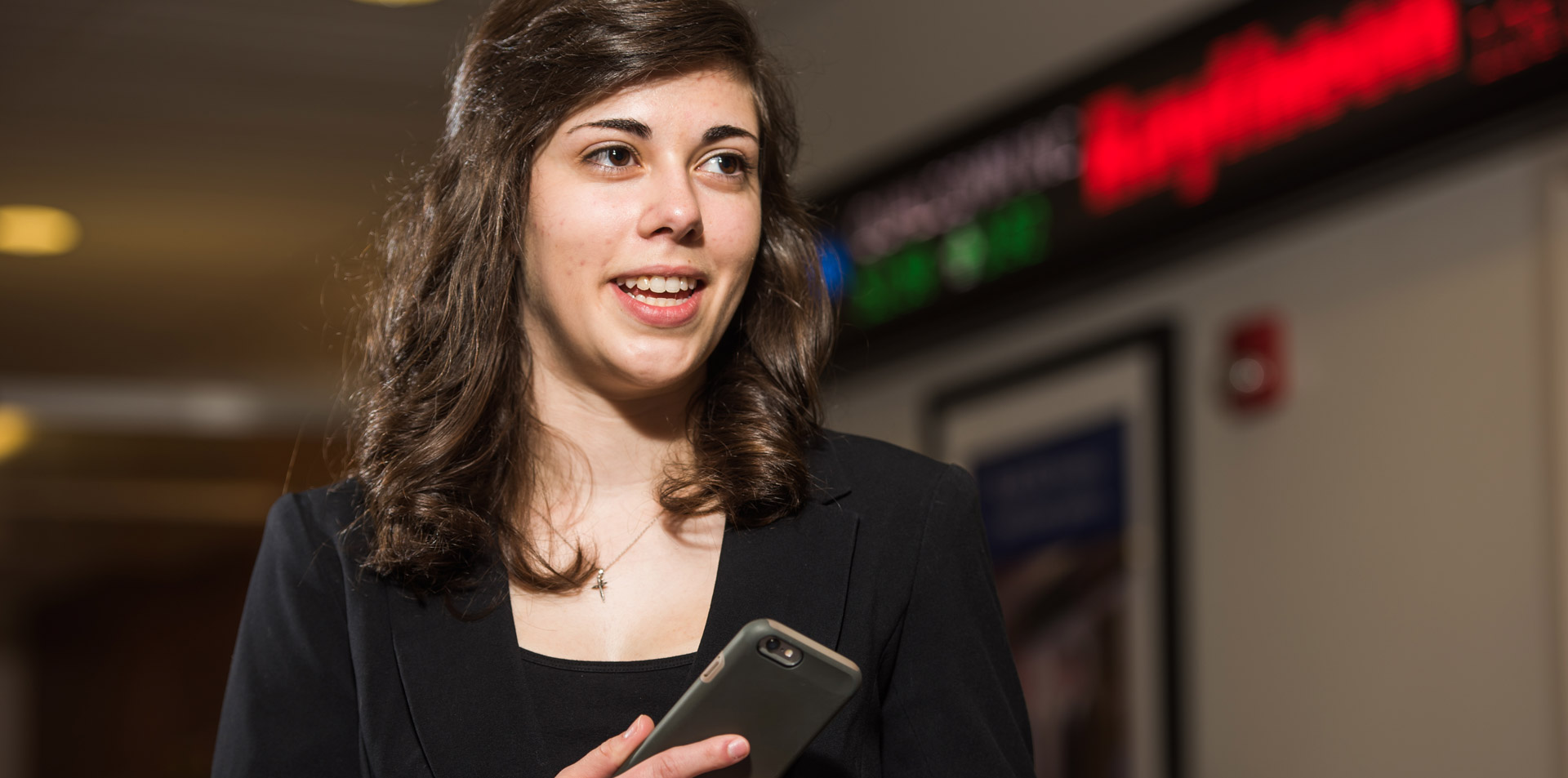 Student photographed near the electronic ticker outside Behrend's simulated trading floor