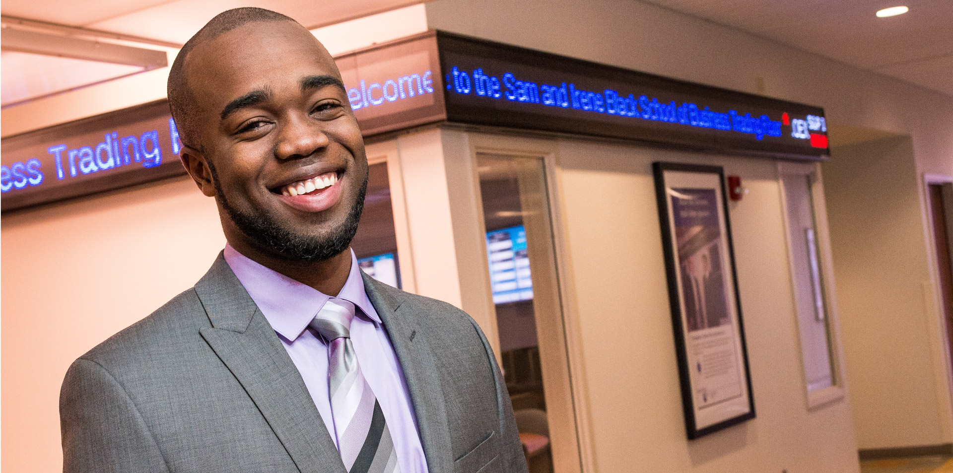 Student smiling in front of the electronic ticker outside Behrend's simulated trading floor lab