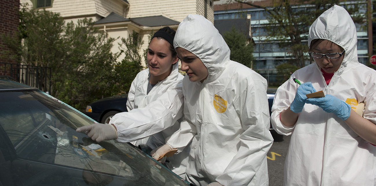 At a mock crime scene students dressed in protective gear examine bullet holes in windshield