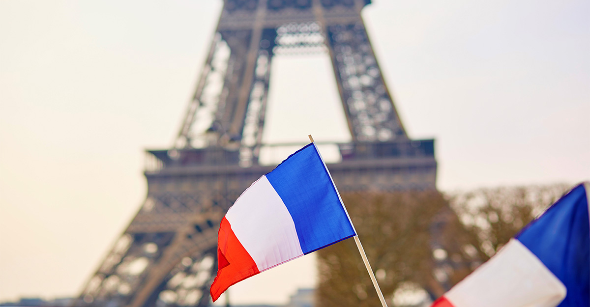 Close up of the French flag in front of the Eiffle Tower
