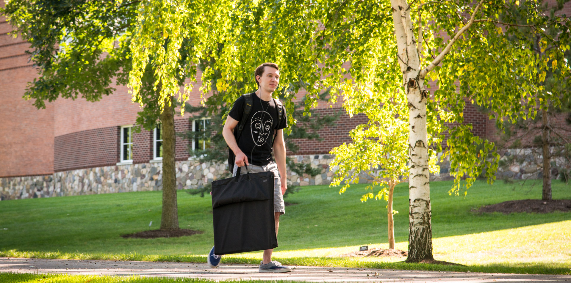 Student holding a portfolio walking in front of Lilley Library