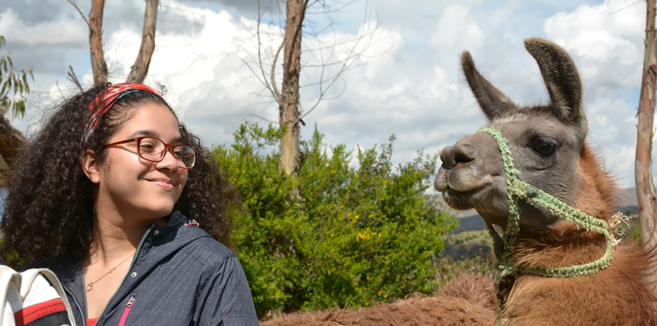 Student smiling at llama in Peru