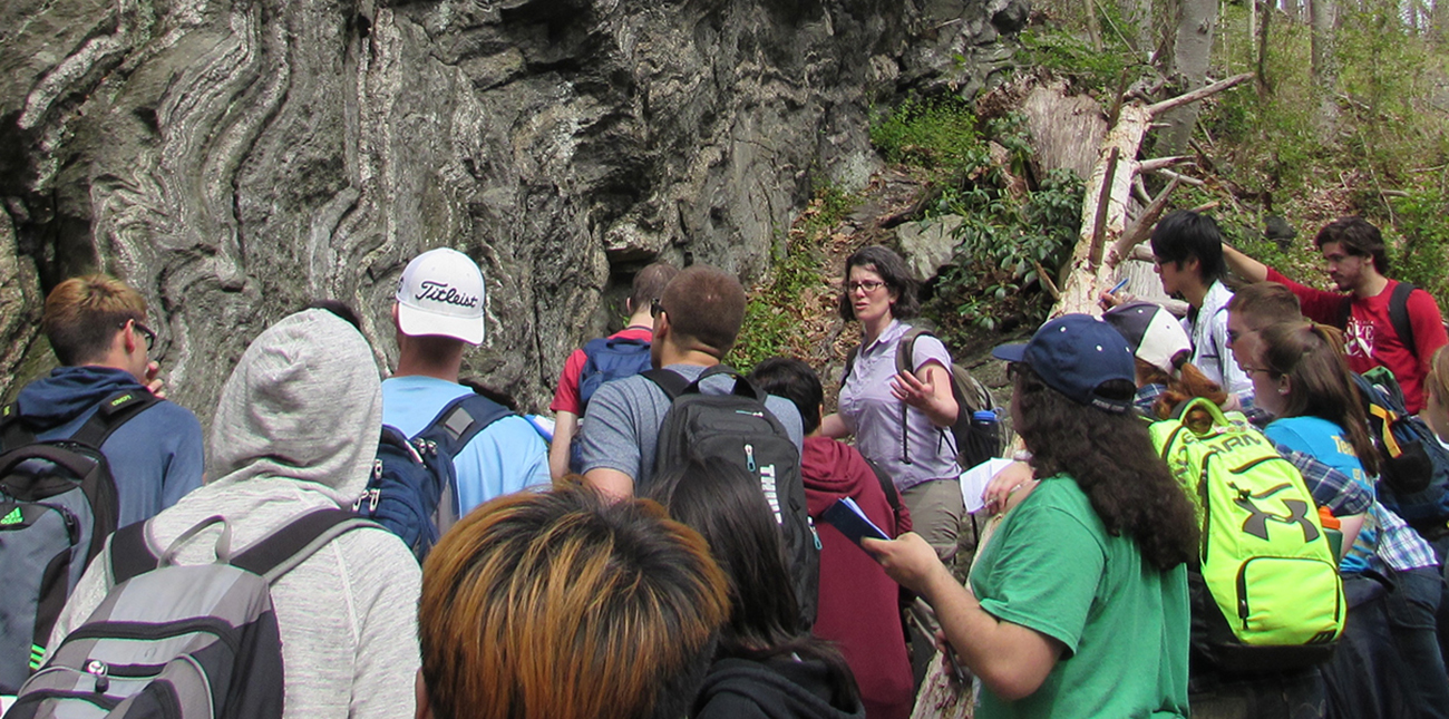 Students viewing rock formation with instructor