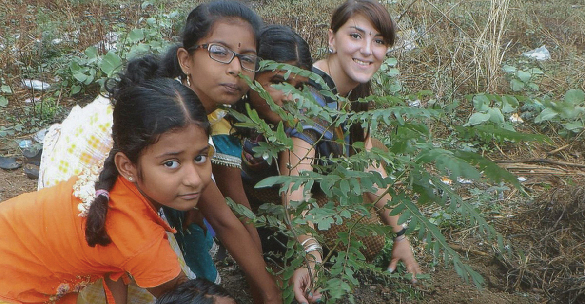 Student working with three children in India to plant a garden