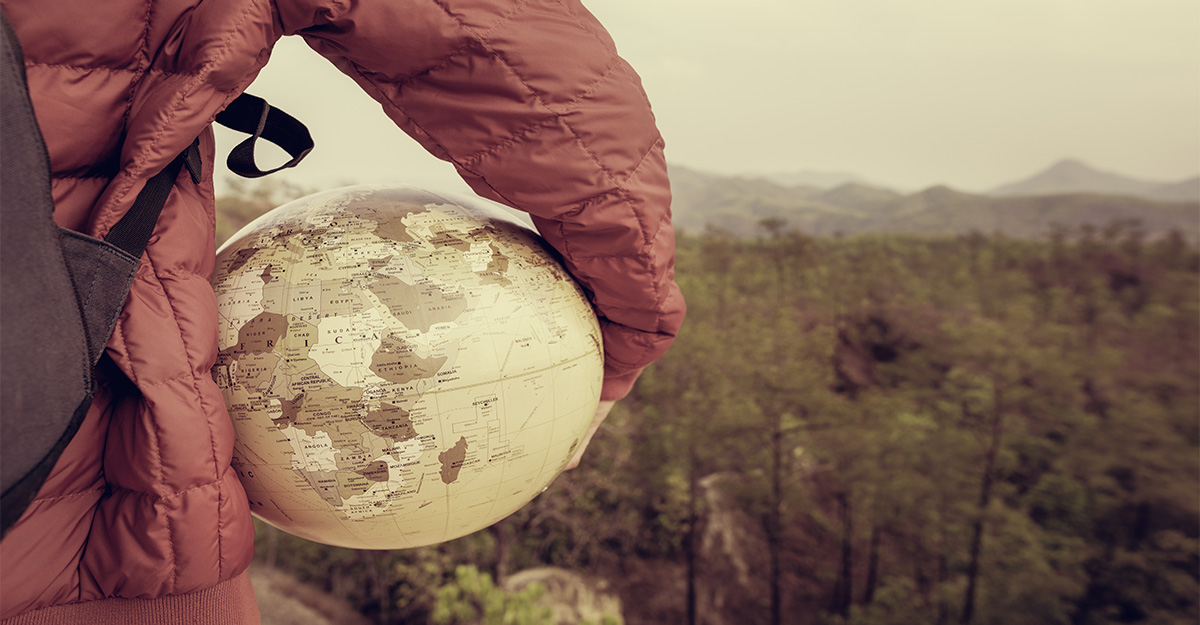 Student standing on a mountain top with globe