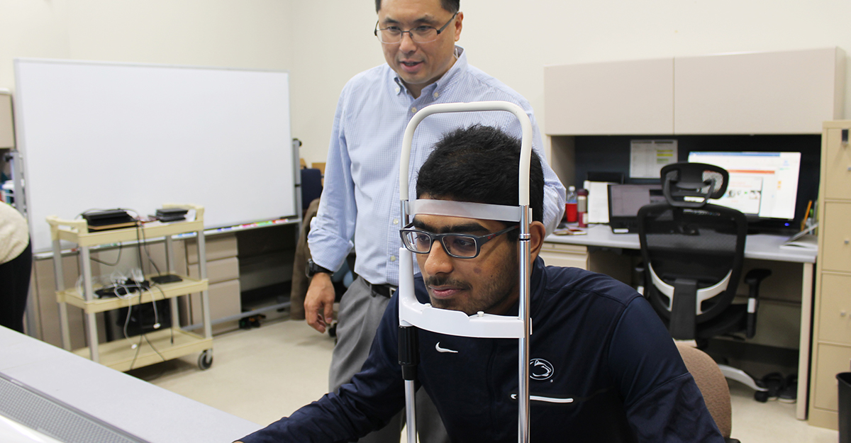 Engineer doing research about human interaction with machines with person sitting in vision test chair