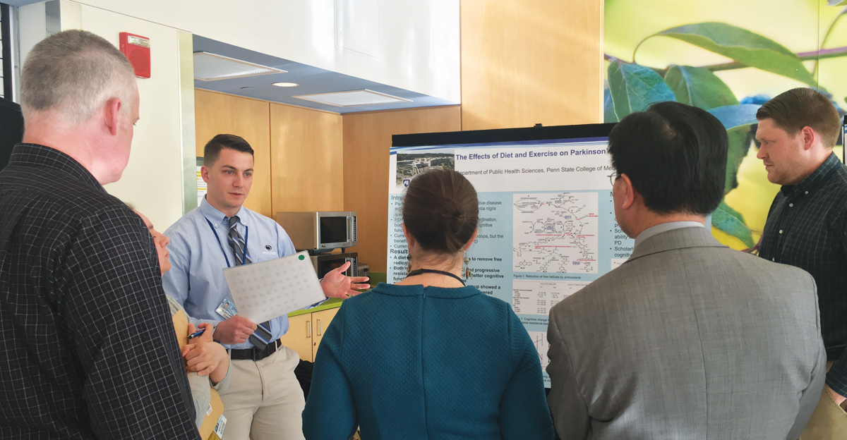 A Penn State student discusses his poster presentation on the effects of exercise on Parkinson during an on-campus event for National Public Health Week.