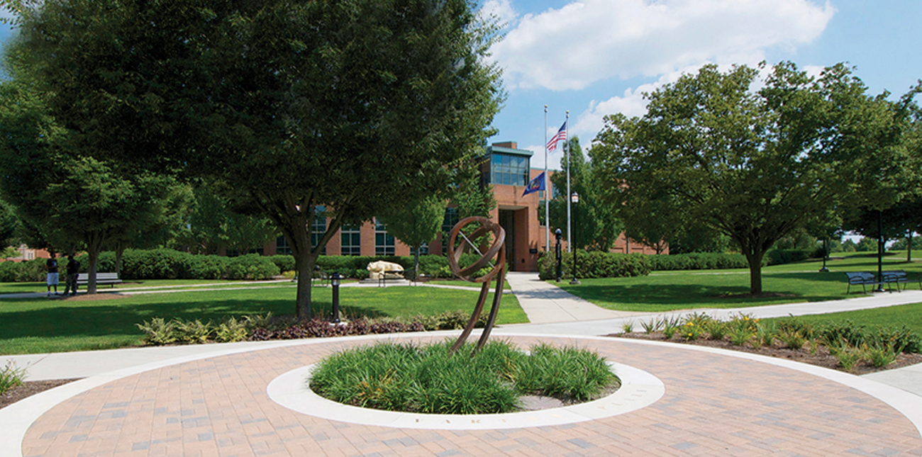 Sculptural sundial in center of campus quad with the Library in the background