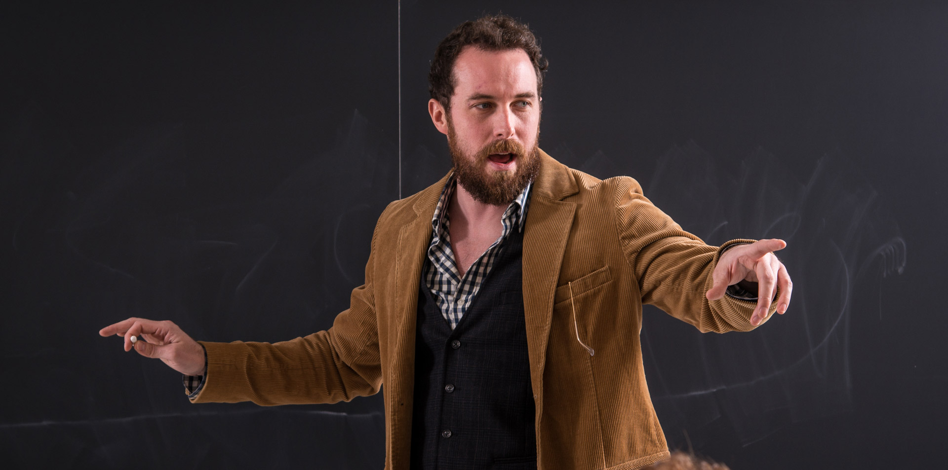 Faculty member standing at a chalkboard gesturing to a student