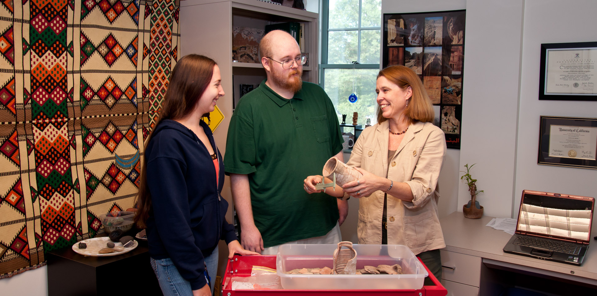 Professor demonstrating to two students how to measure a very old clay jar