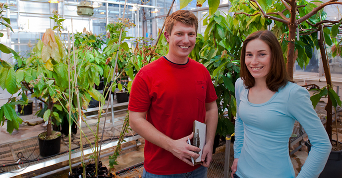 Male and female student in greenhouse with plants.