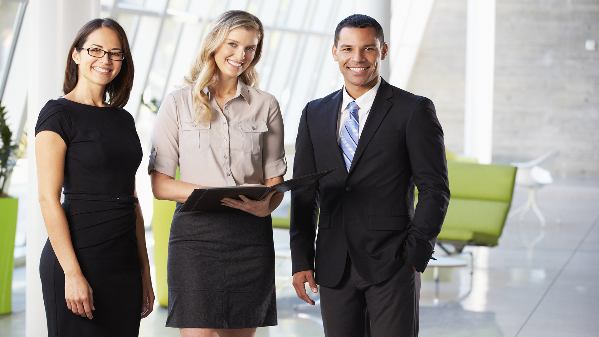 Three students in business attire preparing for a meeting