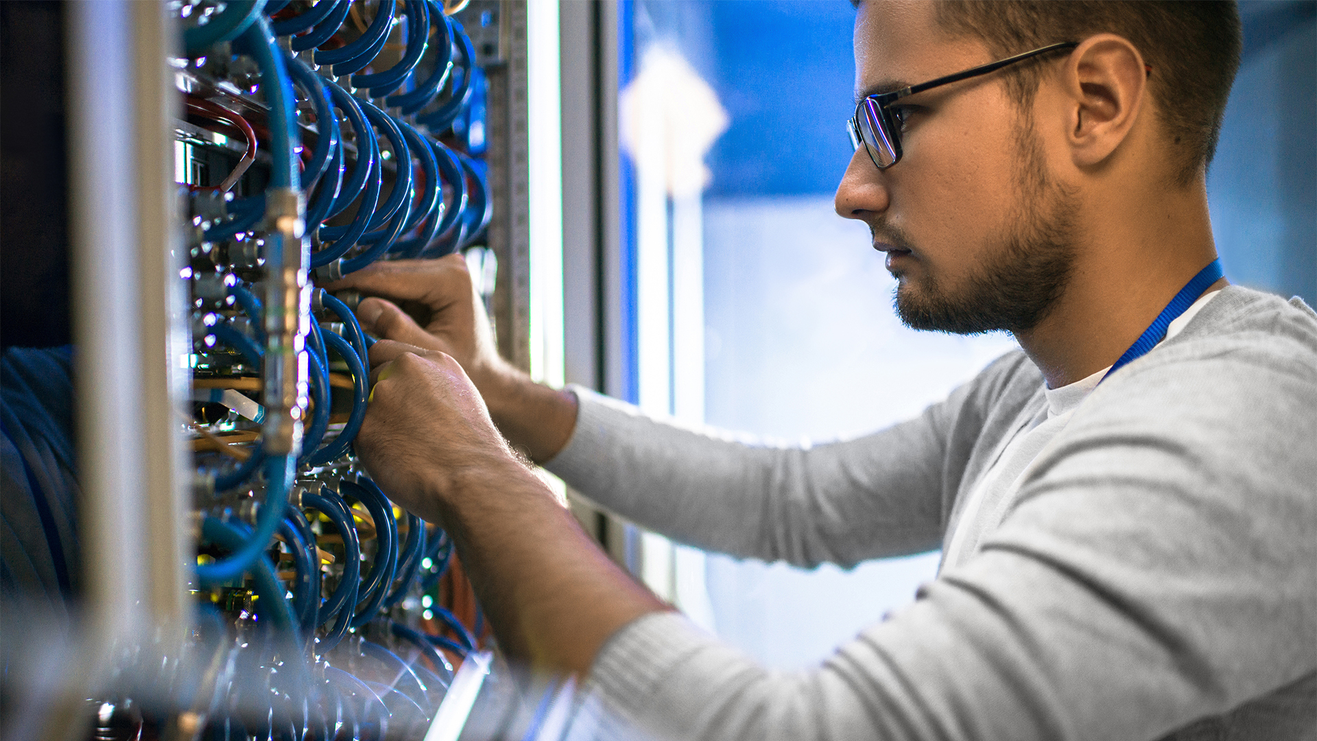 Student connecting cables in server cabinet while working in supercomputer data center