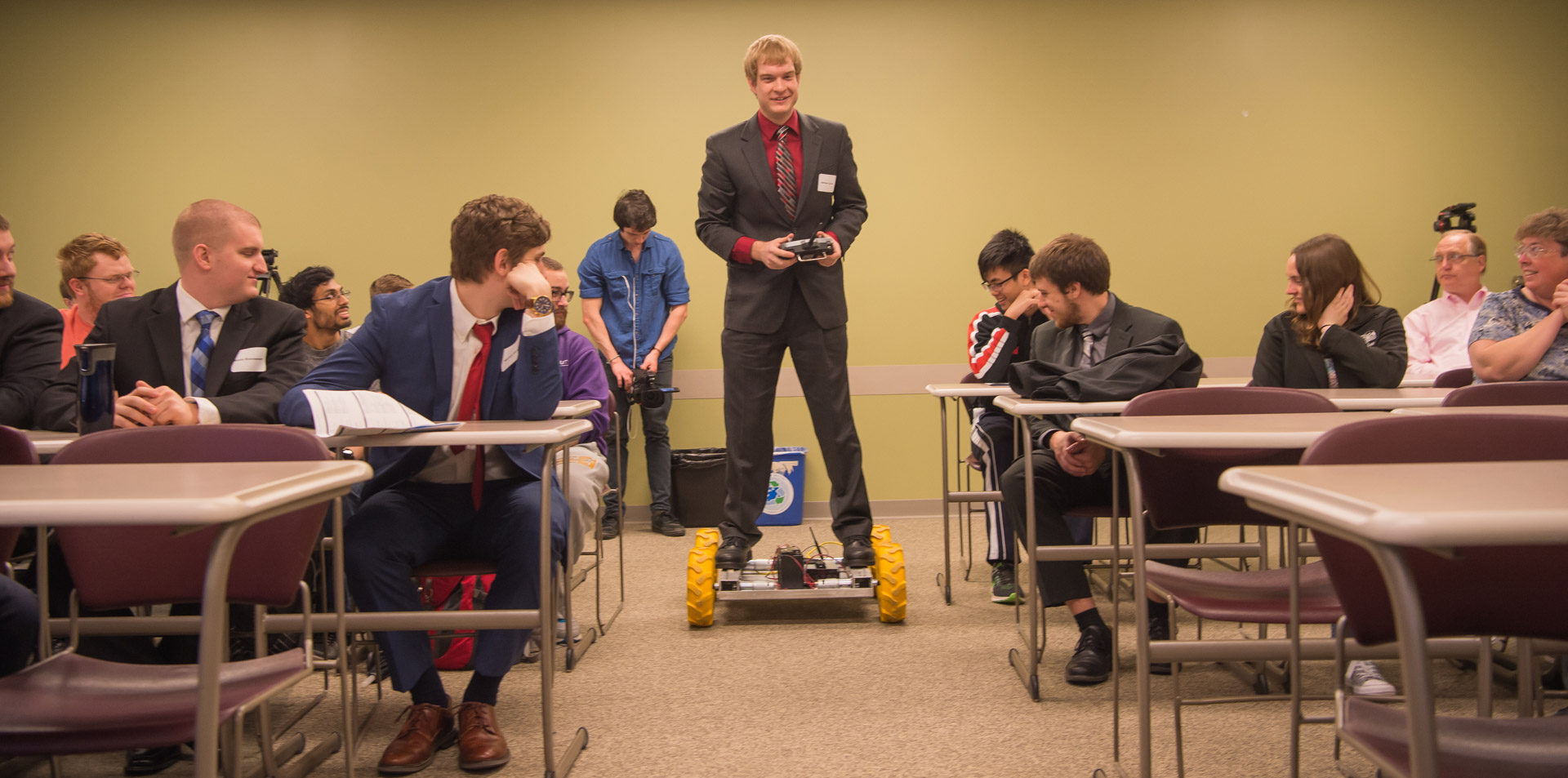 A class looking at a student standing atop a small four-wheeled platform