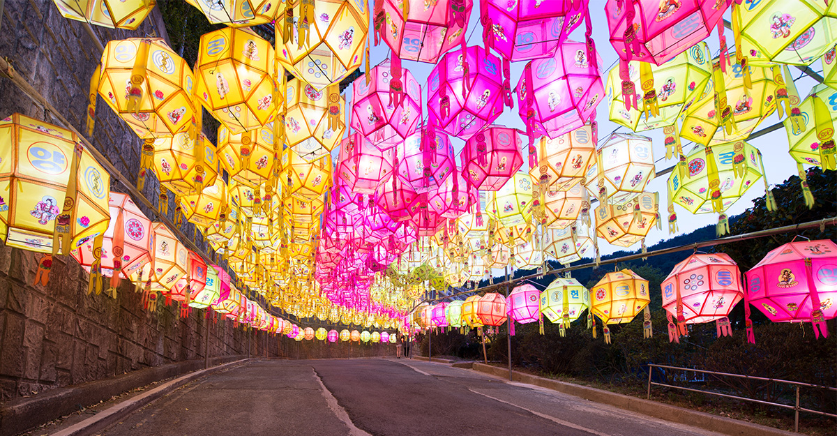 Pink and yellow Korean lanterns hanging in the street