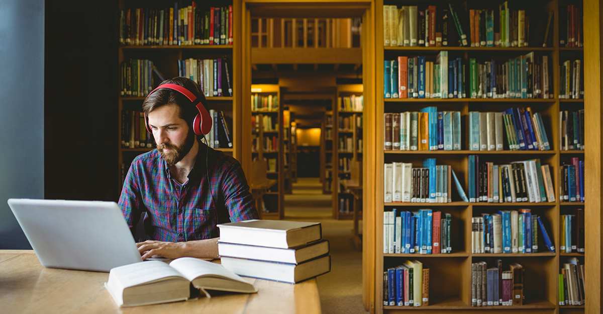 Student works in library with headphones on