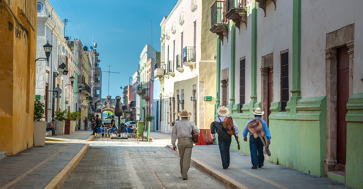 Mariachi group walks a colorful street in colonial Campeche, Mexico