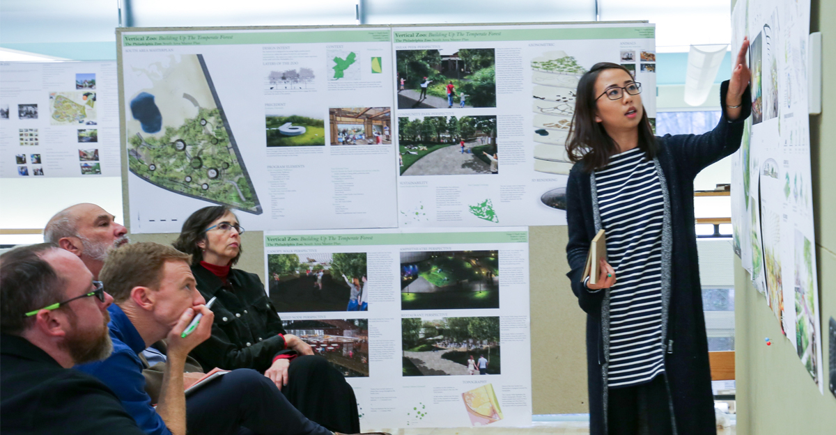 Graduate education in landscape architecture at Penn State promises research-based design projects and engaged critique through peer review. Pictured: a student gesturing toward a pin-up board articulating her landscape architecture design work to a captivated jury during her final review.